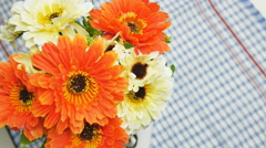 Orange artificial flowers on the dining table Stock Footage