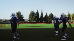 Football players warming up before a game Stock Footage