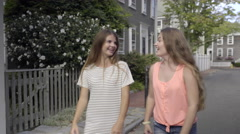 Girl Gives Friend A Piggyback Ride Down New England Neighborhood Street Stock Footage