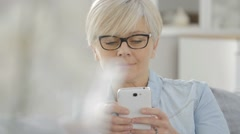Senior woman with eyeglasses sending text message - stock footage