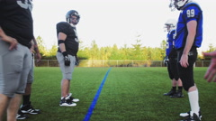 Football players running a play on the field Stock Footage