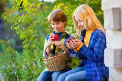 Happy kids eating fruits from picnic basket outdoor. romantic or first love Stock Photos