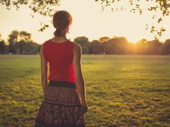 Woman standing in park admiring the sunset Stock Photos