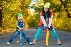 Stock Photo of Smiling woman and boy standing width color plastic penny board skateboard
