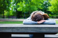 Sad young woman at table in park - stock photo