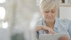 Senior woman websurfing on digital tablet Stock Footage