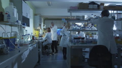 Group of caucasian scientists in white coats are working in a modern laboratory - stock footage