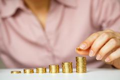 Female hand stacking gold coins into increasing columns - stock photo