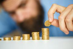 Male hand stacking gold coins into increasing columns - stock photo
