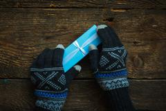 Hands in winter gloves with christmas gift box - stock photo