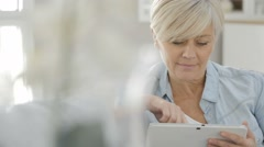 Senior woman websurfing on digital tablet - stock footage