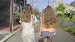 Teens Hold Hands, With Their Pinky Fingers, And Walk Down Neighborhood Street Stock Footage