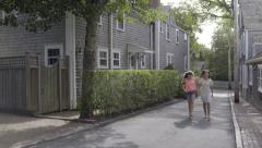 Friends Hold Hands/Skip In Middle Of Road In New England Neighborhood Stock Footage