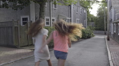 Teens Hold Hands And Skip Down Middle Of Road In New England Neighborhood - stock footage