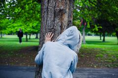Hooded person hiding behind a tree - stock photo