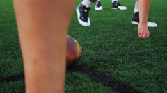 Close up of a football being passed off at the line of scrimmage Stock Footage