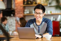 Happy cheerful asian male smiling and using laptop in cafe - stock photo