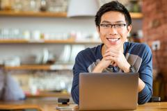 Positive asian male in glasses with laptop Stock Photos