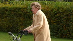 Pensioner wheel walker in autumn park side view Stock Footage