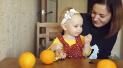 Child with her mother are eating tangerin Stock Footage