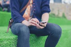 Woman sitting on astro turf using smart phone Stock Photos