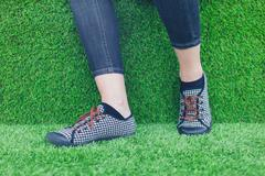 Feet of young woman on astro turf - stock photo