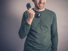 Happy young man with vintage phone - stock photo