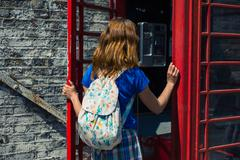 Young woman entering a phone booth - stock photo