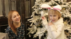 Happy baby girl celebrates Christmas and New year in fur suit of white bunny. Stock Footage