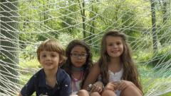 Close up of mixed brothers and sister sitting and laughing together in hammock Stock Footage