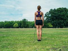 Woman in park exercising with jump rope Stock Photos