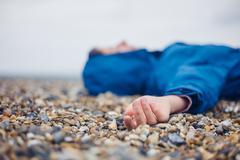 Unconscious woman on shingle beach - stock photo