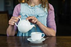 Woman pouring tea at table in dining room Stock Photos