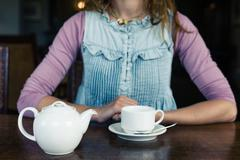 Young woman having tea in dining room Stock Photos