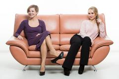 beautiful female friends on the sofa. two businesswomen. body language, gestures - stock photo