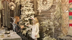 Mother and daughter in white costume of rabbit decorate the Christmas tree. Stock Footage