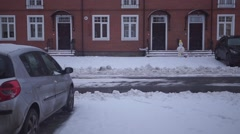 Snowing in front of red brick townhouses Stock Footage
