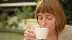 Drinking coffee - Beautiful young woman sitting at the mall cafe Stock Footage