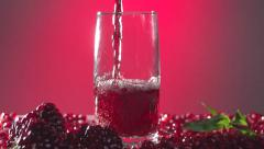 Garnet. Pomegranate juice is poured into a glass. - stock footage