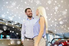 Happy couple buying car in auto show or salon Kuvituskuvat