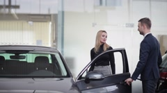 Handsome young car salesman assisting a client - stock footage