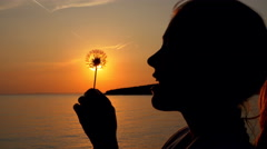 Girl blowing dandelion plant in sunset Stock Footage