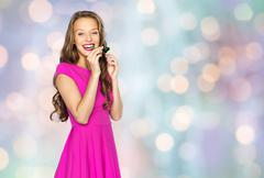 Stock Photo of happy young woman or teen girl with party horn