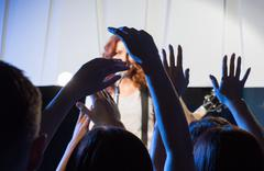 female singer with guitar over happy fans hands - stock photo
