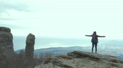 Tourist on top of mountain. Girl in raincoat relax and enjoy beautiful panorama - stock footage