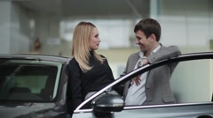 Happy young couple in car dealership - stock footage