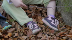 Cute little female child playing with yellow fallen leaves,tilt up,close up. Stock Footage