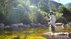 Man fly-fishing in a river Stock Footage