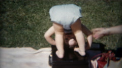 1955: Curious baby looking between legs somersaults with help of mom. Stock Footage