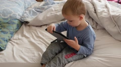 Dolly shot of a boy using iPad on a bed Stock Footage